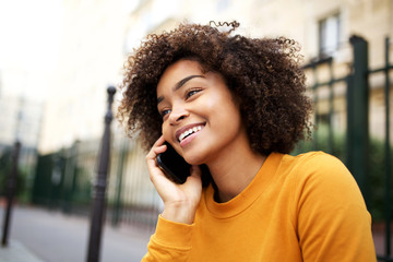 happy african american young woman talking with cellphone in city