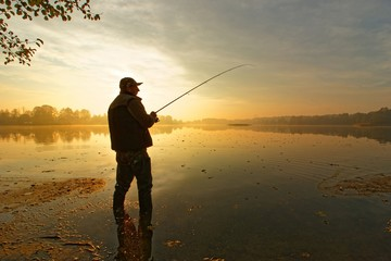 angler catching fish in the lake during cloudy sunrise