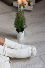 White knitted socks on female feet against little Christmas tree. Holiday and New Year concept.