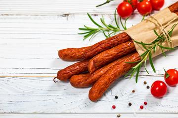 Kabanos or Cabanossi Thin Dry Smoked Polish Sausage on White Wooden Background. Selective focus.