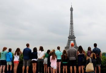 Grupa ludzi stojących i patrząc na Wieżę Eiffla