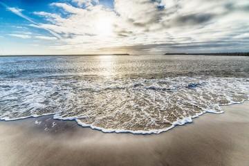 Piękny strzał ocean woda przyjeżdża brzeg i chmurnego niebo w tle