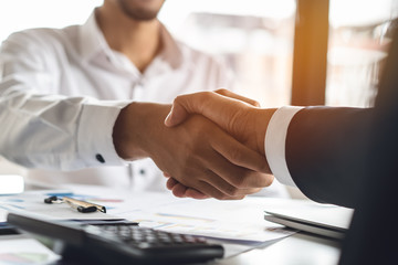 Banker and client shaking hands after business loan grant.