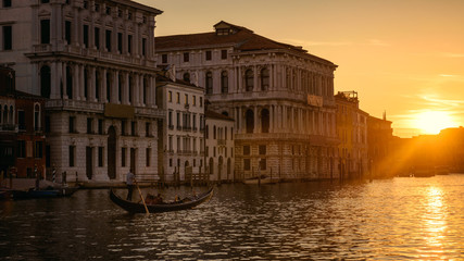 Venice at sunset, Italy. Gondola with tourists sails on Grand Canal at night. Panorama of Venice city in evening light. Scenery of sunny street in the Venice center. Romantic water trip at dusk.