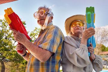 Modern Senior couple have fun playing with  water gun.