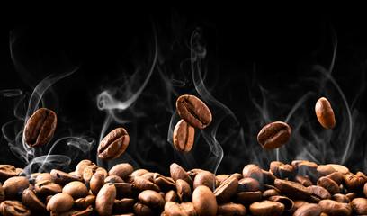 Ziarna kawy spadają w dym na czarnym tle. Palenie kawy