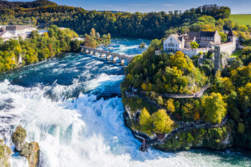 Rhine Falls or Rheinfall, Switzerland panoramic aerial view. Tourist boat in waterfall. Bridge and border between the cantons Schaffhausen and Zurich. Cliff-top Schloss Laufen castle, Laufen-Uhwiesen