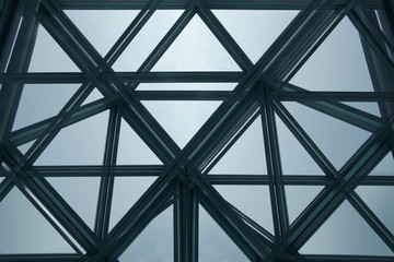 Modern architecture fragment with structural glazing. Backlit glass ceiling, roof or wall consisting of transparent panels. Abstract geometric background with polygonal pattern.