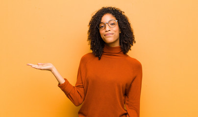 young pretty black woman feeling happy and smiling casually, looking to an object or concept held on the hand on the side against orange wall