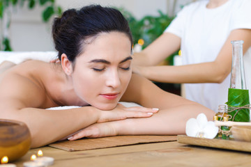 Young pleased woman is getting thai massage, therapy. Female hands of master are kneading back of client. Brunette girl is lying on couch in light spa ayurveda salon. Relax and health care concept.
