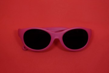 Pink plastic sunglasses isolated on red background.