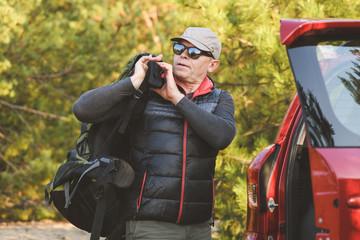 Elderly man tourist prepare for car travel