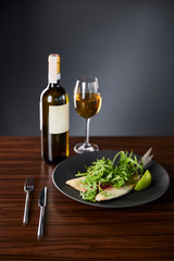 tasty restaurant fish steak with lime and arugula on wooden table near cutlery and white wine on black background