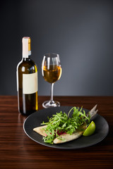 tasty restaurant fish steak with lime and arugula on wooden table near white wine on black background
