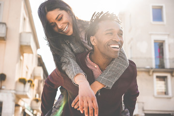 African couple having fun outdoor in city tour - Young people lovers enjoying time together during vacation journey - Love, fashion, travel and relationship concept - Focus on woman face