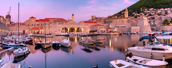 Panoramic view of Old Harbour with boats and Old Town of Dubrovnik at sunset, Croatia