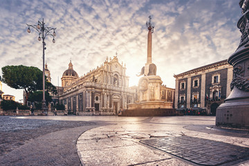 """Catania Dome Square at the sunset and the famous landmark elephant fountain also know as """"liotru"""" by the indigene people. Cloudy sky and marvelous sun light."""