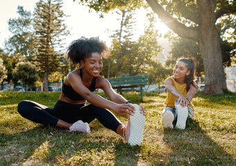 Young diverse female friends sitting on green grass stretching her legs in the morning sunlight at park - diverse friends warming up before doing group exercise