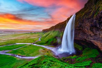 Sunrise on Seljalandfoss waterfall on Seljalandsa river, Iceland, Europe. Amazing view from inside. Landscape photography