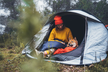 tourist traveler hugging relaxation red shiba inu in camp tent on background foggy forest, smile hiker woman with puppy dog in mist nature trip, friendship love concept, girl resting dog together