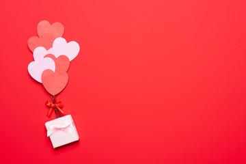 Valentine's day background with red and pink hearts like balloons on pink background, flat lay