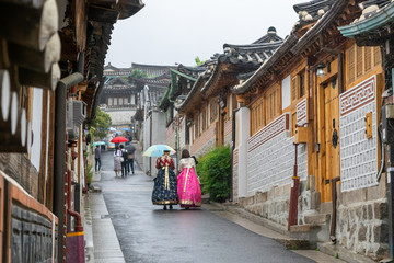 Women dressed in traditional Korean clothing in historic Hanok Village on rainy day - Seoul, South Korea