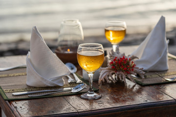 Two wine glasses on wooden table near sea on the tropical beach during sunset