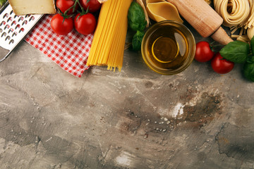 Pasta, vegetables, herbs and spices for Italian food on rustic table