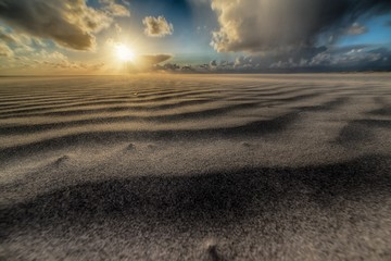Beautiful shot of the sun rising over a sandy beach at the seashore