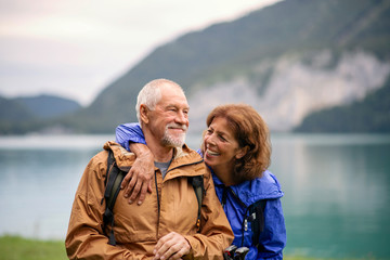Senior pensioner couple hiking by lake in nature, resting.