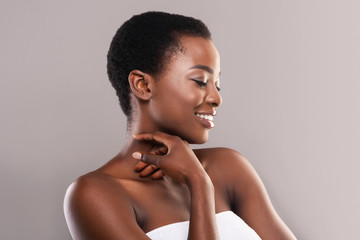 Beautiful black girl touching her velvet skin on neck
