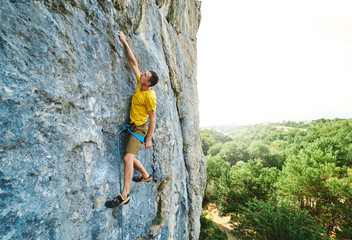 Young strong man climbing challenging route on a high vertical limestone cliff.
