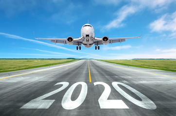 The inscription on the runway 2020 surface of the airport runway with take off aircraft. Concept of travel in the new year, holidays.