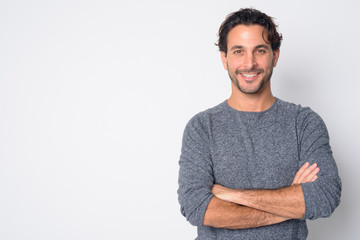 Portrait of happy handsome Hispanic man smiling with arms crossed