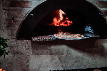 Italian chef is putting prepared margarita pizza to the oven with flame in it.