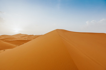 Desert landscape with orange dunes and blue sky at sunset.