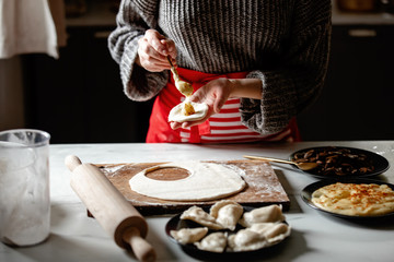 woman cooking  polish dumplings at kitchen