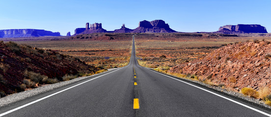 Road into the red rock desert landscape of Monument Valley, Navajo Tribal Park in the southwest USA in Arizona and Utah