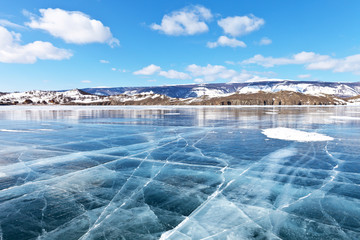 Sunny winter day on Lake Baikal. Blue clear ice with cracks in the Small Sea Strait. Wooden landmarks marked the ice road. On the shore of wooden houses of tourist camps