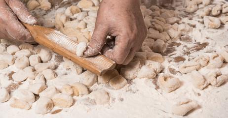 Hands kneading dough for gnocchi.