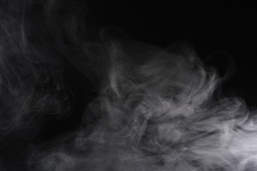 Puffs of white, gray smoke spread on a black background, curling in a fancy dance.