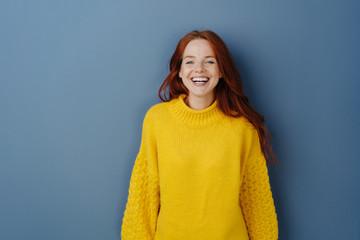 Joyful young redhead woman laughing at camera
