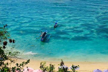 boat on white sand beach in bali -indonesia