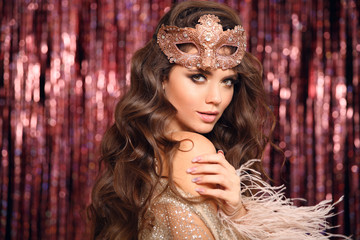 Christmas holiday party. Beautiful brunette with Healthy wavy hair. Fashion Beauty Girl with carnival mask Isolated on golden bokeh lights Background. Glamour Makeup. Jewelry copy space. Hairstyle.
