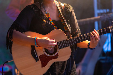 close-up view of musician woman playing guitar on the stage, female guitarist hands during night live music performance