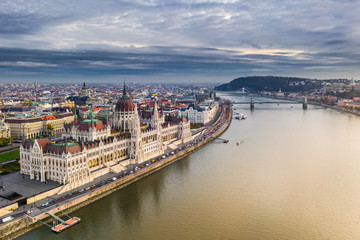 Budapest, Hungary - Aerial view of the beautiful Parliament of Hungary at sunset with golden lights and sightseeing boats on River Danube. Szechenyi Chain Bridge, St. Stephen's Basilica at background