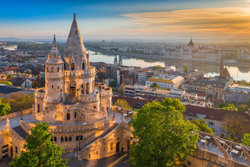Budapest, Hungary - Beautiful golden summer sunrise with the tower of Fisherman's Bastion and green trees. Parliament of Hungary and River Danube at background. Blue sky.