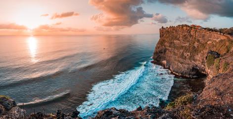 Piękny panoramiczny widok słynnego słynnego miejsca Uluwatu Temple, podczas tętniącego życiem letniego wschodu słońca. Znajduje się na Bali, Indonezja