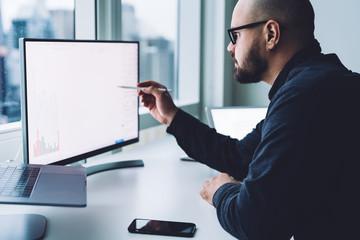 Man looking at graph on computer