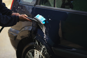 Rigid brush in the hands of a person and water splashes during car washing, close-up.